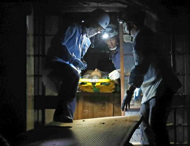 Une victimes des intempéries est évacuée de sa maison par les secours le 9 juillet 2018à Kurashiki. [JIJI PRESS / JIJI PRESS/AFP]