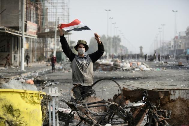 Un manifestant irakien brandit le drapeau national, dans la ville sainte de Najaf, le 1er décembre 2019 [Haidar HAMDANI / AFP]