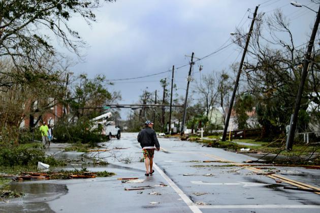 Un homme marche dans les rues de Panama city (Floride) après le passage de l'ouragan Michael, le 10 octobre 2018. [Brendan Smialowski / AFP]