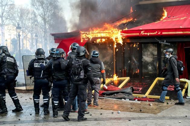 Les forces de police devant Le Fouquet's en feu, sur les Champs Elysées, à Paris, le 16 mars 2019 [Zakaria ABDELKAFI / AFP/Archives]