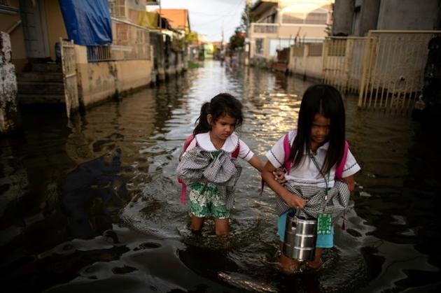 Des écolières pataugent dans les eaux à Mabalacat (Philippines) le 8 octobre 2018  [Noel CELIS / AFP]