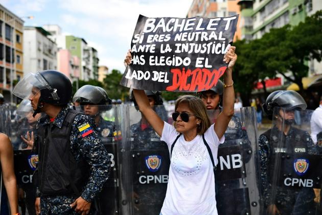 """Une partisane de Juan Guaido manifeste à Caracas le 9 mars 2019 avec une banderole disant """"Bachelet, si tu restes neutre face à l'injustice, tu as pris le parti du dictateur"""", adressée à Michelle Bachelet, Haut-Commissaire de l'ONU aux droits de l'homme [RONALDO SCHEMIDT / AFP]"""