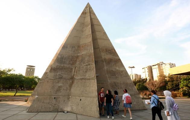 Des visiteurs au pied d'un des bâtiments conçus par l'architecte brésilien Niemeyer à Tripoli au Liban, le 3 octobre 2018 [ANWAR AMRO / AFP]