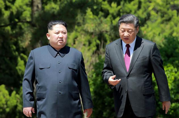 Photo fournie le 9 mai 2018 par l'agence nord-coréenne Kcna du leader nord-coréen Kim Jong Un (g) et du président chinois Xi Jinping, lors d'une rencontre à Dalian le 8 mai 2018, en Chine [KCNA VIA KNS / KCNA VIA KNS/AFP/Archives]