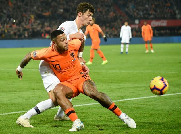 Le Néerlandais Memphis Depay (gauche) tente de récupérer le ballon face au défenseur français Benjamin Pavard  [John THYS / AFP]