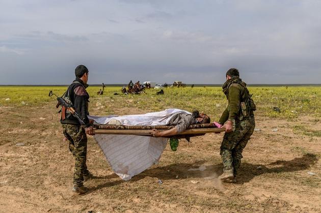 Des combattants des Forces démocratiques syriennes portent sur un brancard un homme blessé soupçonné d'appartenir au groupe Etat islamique, qui a quitté le dernier réduit de l'EI à Baghouz, dans l'est de la Syrie, le 5 mars 2019 [Bulent KILIC / AFP]