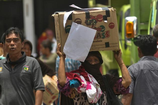 Une femme transporte un colis d'aide après le séisme et le tsunami qui ont frappé l'île des Célèbes, à Palu en Indonésie le 8 octobre 2018 [OLAGONDRONK / AFP]