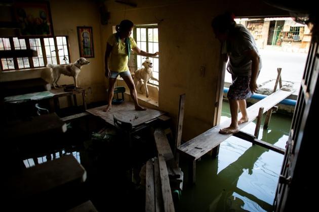 Des habitants se déplacent à l'intérieur d'une maison inondée, le 8 octobre 2018 à Mabalacat, dans la province de Pampanga (Philippines) [Noel CELIS / AFP]