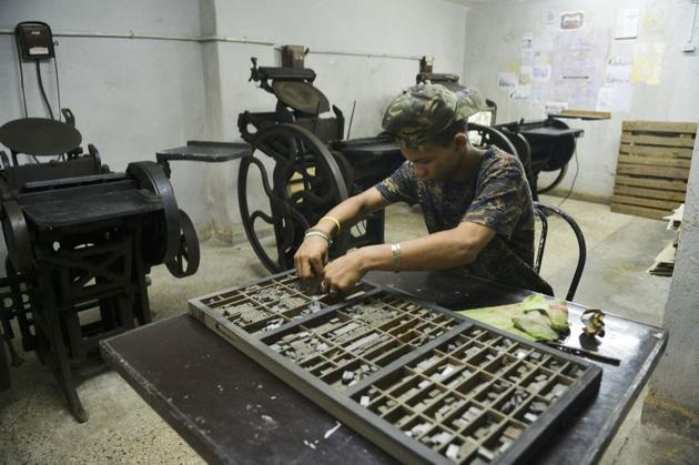 Un employé d'une imprimerie à La Havane prépare une édition en chinois le 13 avril 2019 [Yamil LAGE / AFP]