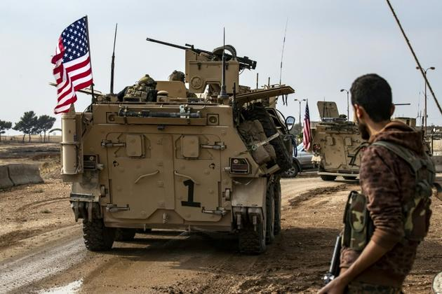 Un combattant des Forces démocratiques syriennes, dominées par les Kurdes, regarde un convoi américain passer près de la ville de Qamichli, dans le nord-est de la Syrie, le 2 novembre 2019 [Delil SOULEIMAN / AFP]