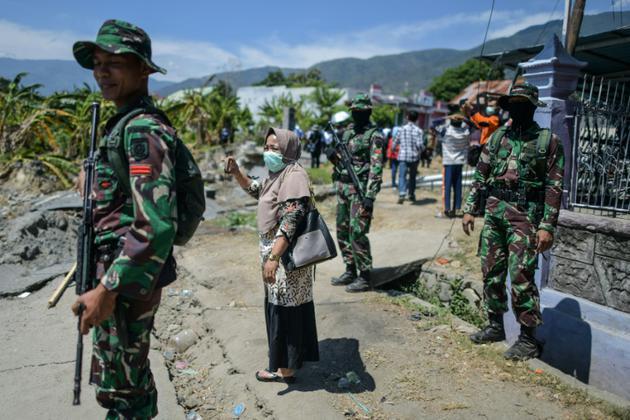Des soldats montent la garde dans le village de Perumnas Balaroa à Palu, le 5 octobre 2018 en Indonésie [MOHD RASFAN / AFP]