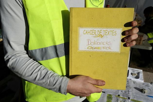 """Un """"gilet jaune"""" montre le cahier de doléances qu'il présente sur un rond-point à Cagnes-sur-mer, le 20 décembre 2018 [VALERY HACHE / AFP/Archives]"""