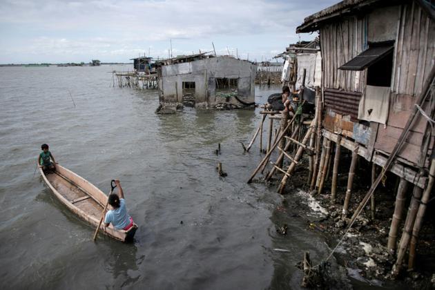 Des habitants de Sitio Paran, dans la province de Bucalan (Philippines), se déplacent en bateau, le 3 février 2019 [Noel CELIS / AFP]