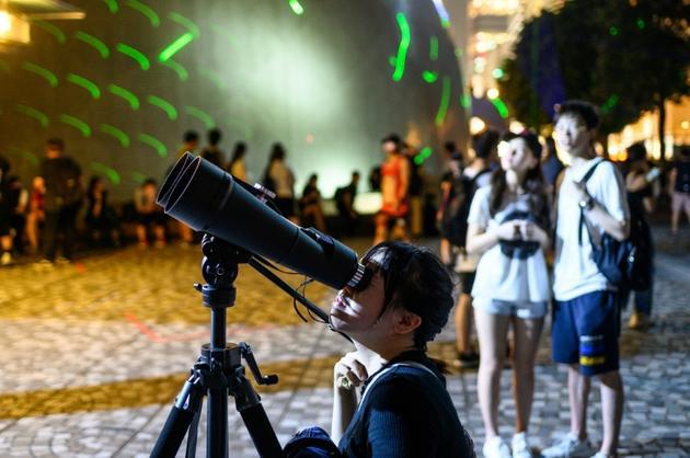 Une manifestante regarde dans un télescope pendant une manifestation en forme de spectacle laser, le 7 août 2019 à Hong Kong [Philip FONG / AFP]