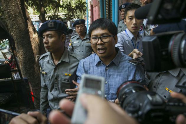 Le journaliste birman Wa Lone (c) escorté par des policiers après son procès à Rangoun, le 4 avril 2018 [SAI AUNG MAIN / AFP/Archives]