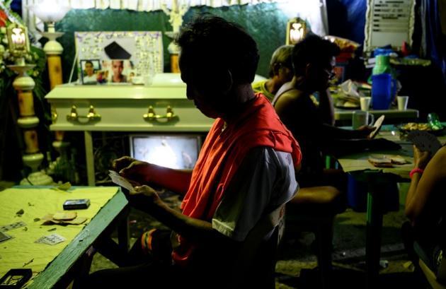 Des proches et des voisins de Bryan Conje, disparu le 2 juillet et retrouvé mort le 5, jouent aux cartes pour lever des fonds destinés à ses obsèques, le 7 juillet 2019 à Manille [Noel CELIS / AFP]