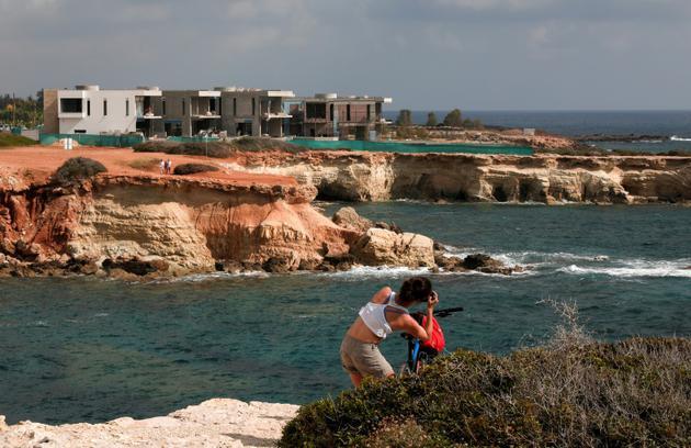 Une touriste prend en photo le 9 mai 2018 six villas de luxe en construction à proximité des grottes marines où ont élu domicile des phoques moines, les mammifères les plus menacés de Méditerranée. Ces villas ont engendré de nombreuses protestations des défenseurs de l'environnement [Emily IRVING-SWIFT / AFP]