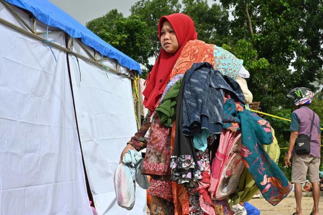 Une femme porte des vêtements donnés par un centre d'aide dans le village de Citangkil à Sumur, le 25 décembre 2018, trois jours après le tsunami qui a frappé l'Indonésie [Adek BERRY / AFP]
