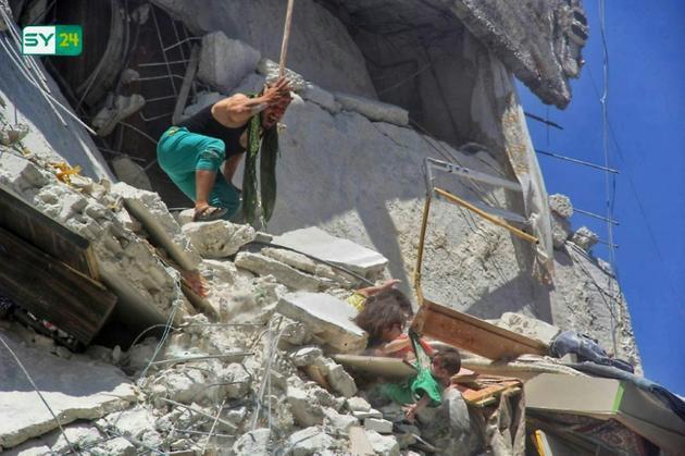 Une image prise par le site d'informations syrien SY24 le 24 juillet 2019 montre trois fillettes suspendues à plusieurs mètres du sol, après un raid aérien à Araha, dans le nord-ouest de la Syrie [Bashar al-Sheikh / SY24/AFP]