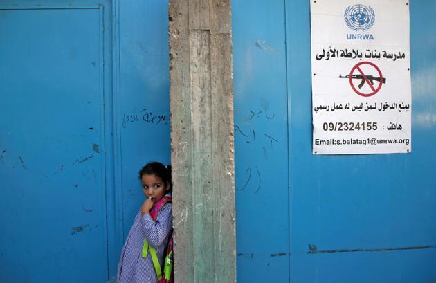 Une élève se tient devant l'entrée d'une école gérée par l'Agence de l'ONU pour les réfugiés (Unrwa) dans le camp de  Balata, à l'est de Naplouse, en Cisjordanie occupée, le 29 août 2018 [Jaafar ASHTIYEH / AFP]