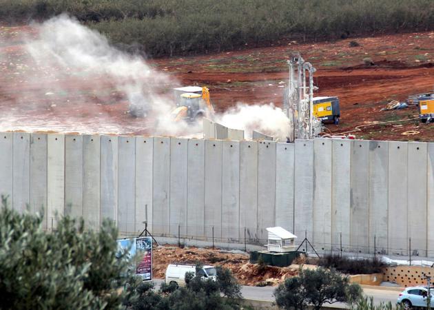 Photo d'un bulldozer israélien en action derrière le mur érigé par Israël à la frontière avec le Liban, le 4 décembre 2018, prise depuis les environs du village libanais de Kfar Kila [Ali DIA / AFP]