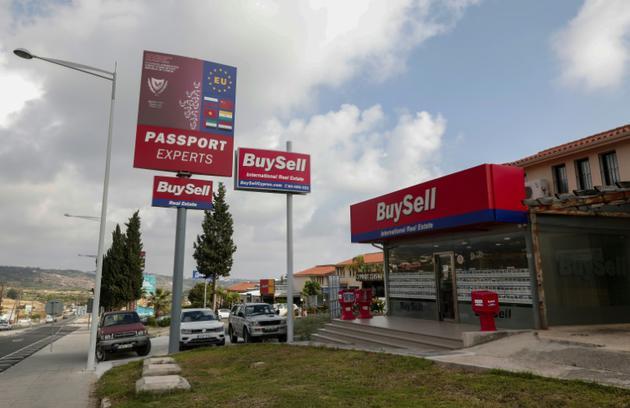 """Une agence immobilière faisant de la publicité à Pegeia, dans l'ouest de Chypre, pour le programme """"investissement contre passeport"""" du gouvernement chypriote. Photo prise le 9 mai 2018 [Emily IRVING-SWIFT / AFP]"""