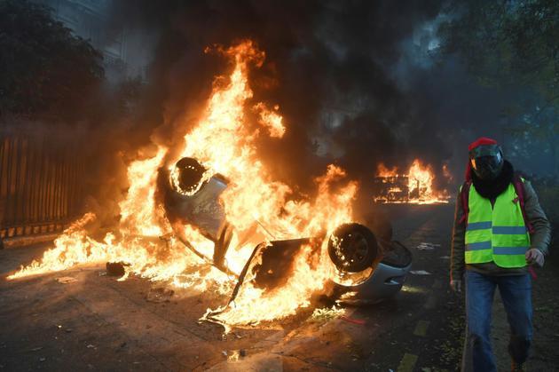 """Voiture en flammes pendant la manifestation des """"gilets jaunes"""", à Paris le 1er décembre 2018 [Alain JOCARD / AFP]"""