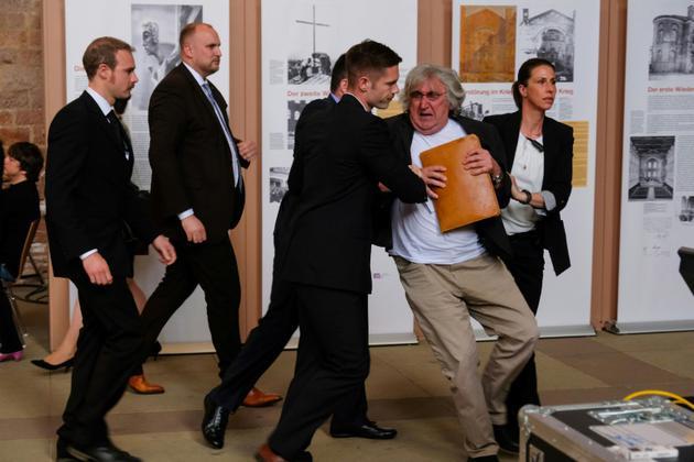 Des agents de sécurité interpellent un manifestant lors d'une cérémonie poure le bicentanaire de Karl Marx à Trèves, en Allemagne, le 4 mai 2018 [Patrik STOLLARZ / AFP]