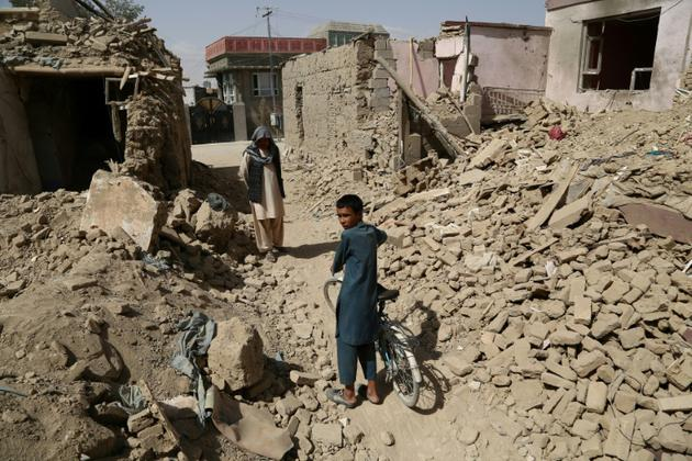 Des Afghans marchent le 16 août 2018 près de maisons détruites à la suite d'une attaque des talibans à Ghazni [ZAKERIA HASHIMI / AFP]