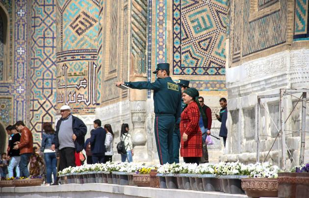 """Des membres de la nouvelle """"Police des touristes"""" renseignent des visiteurs de la ville de Samarcande, le 28 mars 2018 en Ouzbékistan [STR / AFP]"""