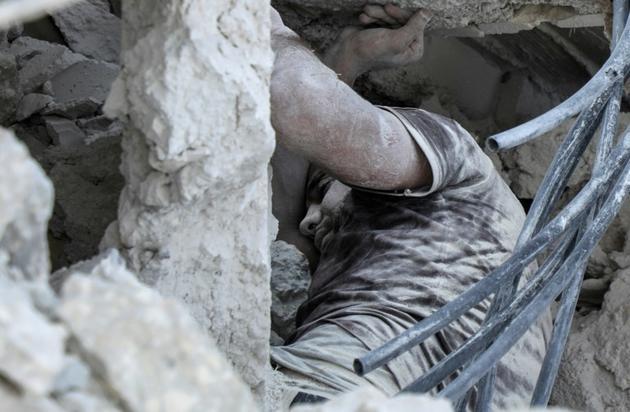 Le corps d'un Syrien dans les décombres d'une construction après une frappe aérienne sur Maaret al-Noomane dans le sud de la province d'Idleb, le 14 août 2019 [Abdullah Hammam / AFP]
