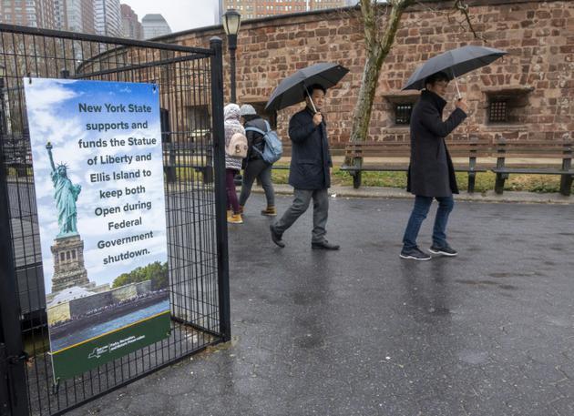 """Des passants devant une pancarte expliquant que New York paie pour garder la Statue de la Liberté ouverte aux touristes, alors que les Etats-Unis entrent dans leur troisième semaine de """"Shutdown"""", le 5 janvier 2019 à New York [DON EMMERT / AFP]"""