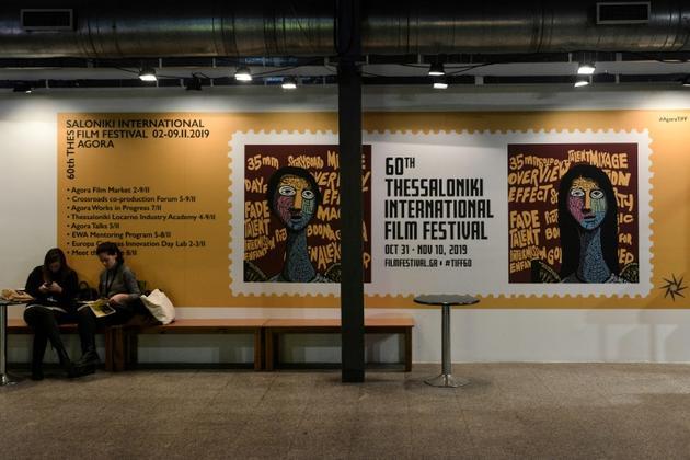 Deux femmes devant une affiche du 60e festival international de cinéma de Thessalonique, dessinée par l'illustrateur John Mavroudis, le 31 octobre 2019 [Sakis MITROLIDIS / AFP]