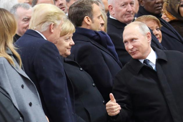Le président russe Vladimir Poutine s'entretient avec son homologue américain Donal Trump, devant la chancelière allemande Angela Merkel, le 11 novembre 2018 à Paris. [ludovic MARIN / POOL/AFP]