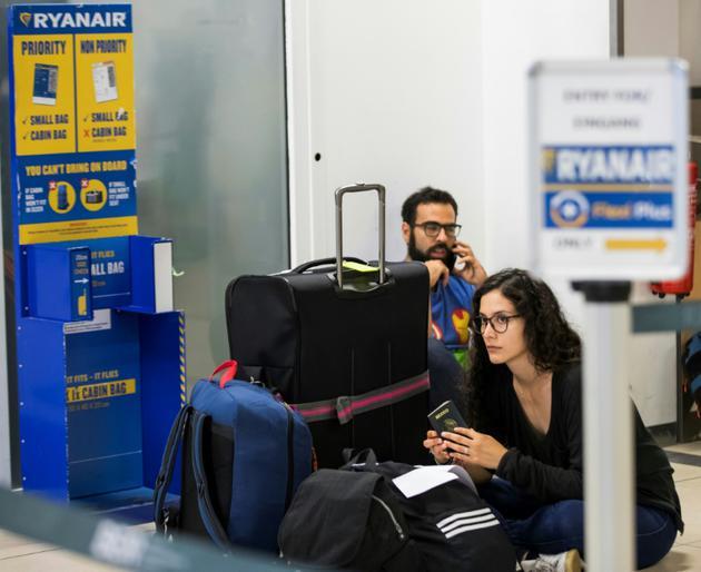 Des passagers de Ryanair attendent après l'annulation de leur vol en raison d'une grève des pilotes, le 10 aoüt 2018, à l'aéroport allemand de Schoenenfeld à Berlin [Odd ANDERSEN / AFP/Archives]