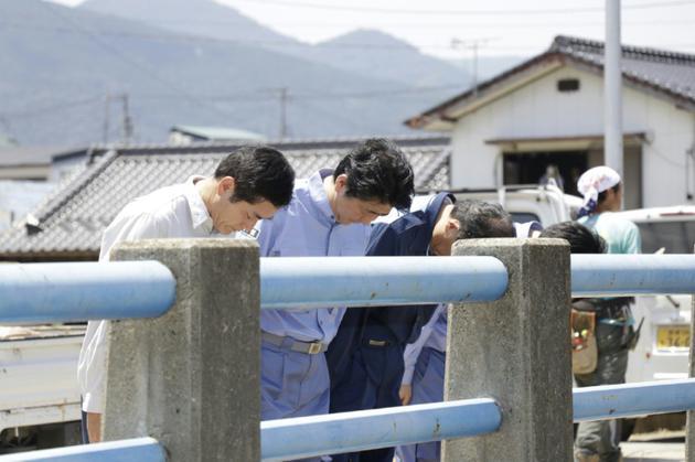 Le Premier ministre Shinzo Abe (2e g) et le gouverneur de la préfecture d'Ehime, Tokihiro Nakamura (g), prient pour les victimes des inondations et glissements de terrain, le 13 juillet 2018 à Seiyo [JAPAN POOL VIA JIJI PRESS / JIJI PRESS/AFP]