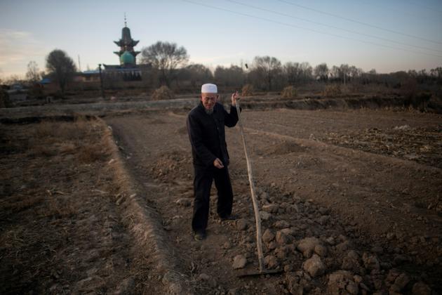Un Chinois musulman travaille dans son champ, une mosquée en arrière-plan, le 2 mars 2018 près de Linxia, dans le nord-ouest de la Chine [Johannes EISELE / AFP]