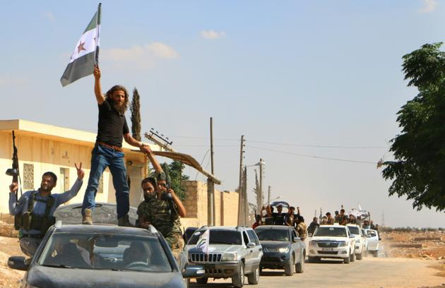 Des combattants rebelles syriens, du Front national de libération (FNL) récemment créé, défilent dans le nord de la province syrienne d'Idleb, après un entraînement militaire, le 11 septembre 2018 [Aaref WATAD / AFP/Archives]