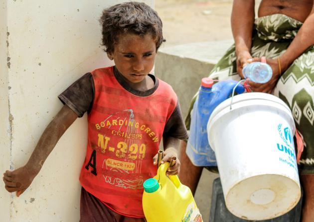 Un enfant yéménite attend son tour pour remplir de l'eau dans un camp de déplacés installé à Khokha pour les habitants ayant fui la ville proche de Hodeida, cible d'une offensive gouvernementale, le 22 juin 2018 [Saleh Al-OBEIDI / AFP]