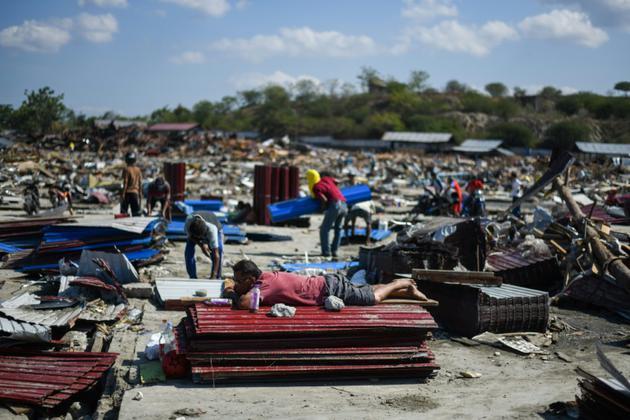 Un homme s'est allongé sur des tôles empilées au milieu des décombres, le 1er octobre 2018 à Palu dans l'île des Célèbes en Indonésie, tandis que d'autres cherchent à récupérer des objets quatre jours après un séisme meurtrier [Jewel SAMAD / AFP]