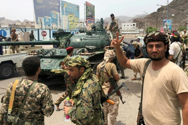 Des séparatistes du sud du Yémen posent devant un char confisqué sur une base militaire gouvernementale à Aden, le 10 août 2019 [Nabil HASAN / AFP]
