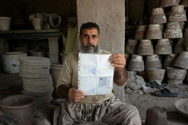 Shirin Agha, artisan potier, montre sa carte d'électeur, le 10 octobre 2018 dans les environs de Jalalabad, en Afghanistan [NOORULLAH SHIRZADA / AFP]