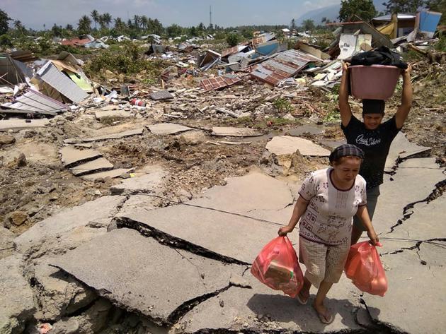 Des indonésiens récupèrent des affaires après un séisme et un tsunami à Palu, dans l'île des Célèbes, le 29 septembre 2018 [MUHAMMAD RIFKI / AFP]