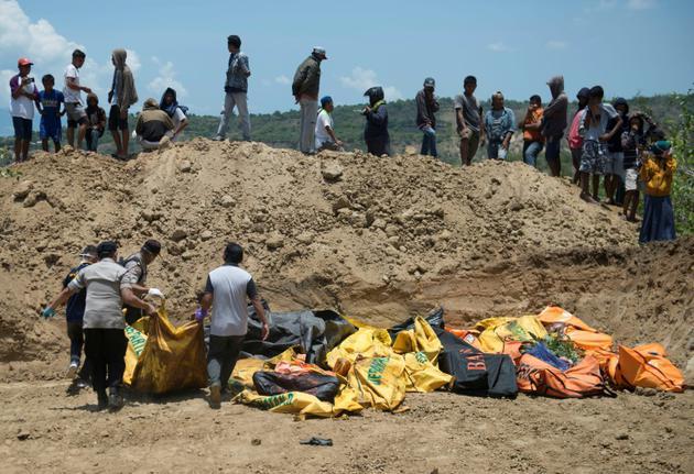 Des corps sont transportés dans une fosse commune avant une cérémonie funéraire pour les victimes du séisme à Palu sur l'île des Célèbes en Indonésie, le 1er octobre 2018 [BAY ISMOYO / AFP]