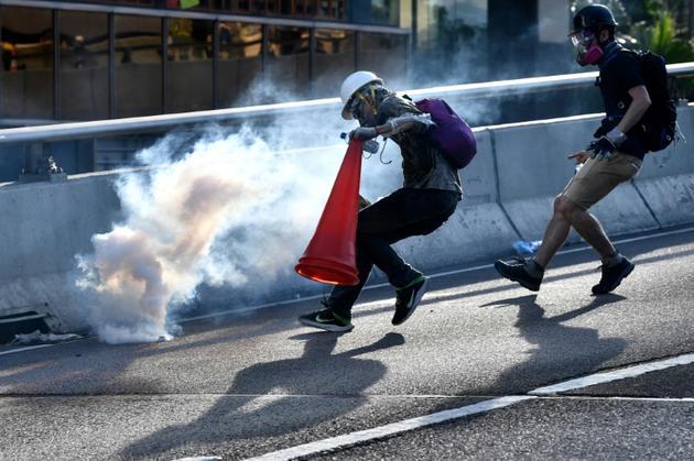 Un manifestant court vers une grenade lacrymogène tirée par la police pour la recouvrir d'un cône de signalisation, le 5 août 2019 à Hong Kong [Anthony WALLACE / AFP/Archives]