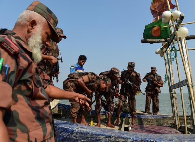 Des douaniers bangladais fouillent un bateau de pêche lors d'une patrouille sur la rivière Naf à Teknaf, le 6 avril 2018 [MUNIR UZ ZAMAN / AFP/Archives]