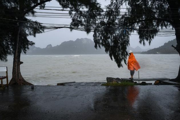 Un homme monte la garde, le 4 janvier 2019, sur un quai vide dans la région de Surat Thani, dans le sud de la Thaïlande, où tous les transports sont immobilisés avant l'arrivée de la tempête tropicale Pabuk [Lillian SUWANRUMPHA / AFP]