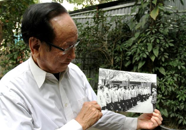 Tran Trong Duyet, anciendirecteurde la prisonde Hoa Lo à Hanoï, montre des photos avec des prisonniers de guerre américains, chez lui à Haiphong dans le nord du Vietnam, le 3 janvier 2018 [Nhac NGUYEN / AFP]