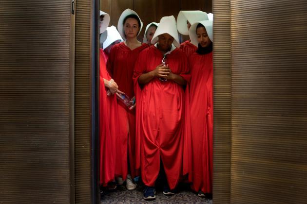 """Des femmes vêtues d'une coiffe blanche et d'une robe rouge, à la manière des personnages du livre et de la série télévisée """"La Servante écarlate"""" (The Handmaid's tale""""), venues protester au Sénat américain contre la nomination du juge Brett Kavanaugh à la Cour suprême au premier jour de son audition, le 4 septembre 2018, avant un vote sur sa confirmation [Jim WATSON / AFP]"""