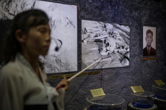 Une guide montre à des visiteurs des photos d'ossements au musée des atrocités de guerre américaines, le 24 juillet 2018 à Sinchon, en Corée du Nord [Ed JONES / AFP]
